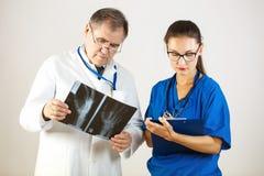 Zwei Doktoren in der Klinik, man betrachtet einen Röntgenstrahl, das andere schreibt zu einer Zeitschrift stockfoto