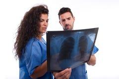 Zwei Doktoren, die einen Röntgenstrahl betrachten lizenzfreie stockfotos