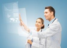 Zwei Doktoren, die mit virtuellem Schirm arbeiten Stockbilder