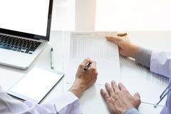 Zwei Doktoren, die Patientenanamnese in einem Büro pointi besprechen stockfotografie