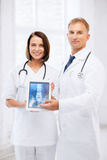 Zwei Doktoren, die Röntgenstrahl auf Tabletten-PC zeigen Stockfotos