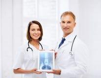 Zwei Doktoren, die Röntgenstrahl auf Tabletten-PC zeigen Stockfoto