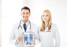 Zwei Doktoren, die Röntgenstrahl auf Tabletten-PC zeigen Stockfotografie