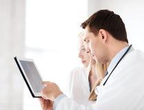 Zwei Doktoren, die Röntgenstrahl auf Tabletten-PC betrachten Lizenzfreie Stockfotos