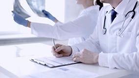 Zwei Doktoren mit Röntgenstrahldrucken und -papieren stock video