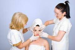 Zwei Doktorholdinghände auf Frauengesicht Lizenzfreie Stockbilder