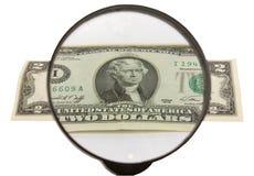 Zwei Dollar und Vergrößerungsglas Stockfotografie