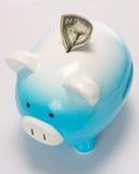 Zwei Dollarschein fest in der Piggy Querneigung Lizenzfreie Stockfotografie