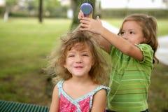 Zwei Doppelschwestern, die vortäuschen, Friseur zu sein stockfoto