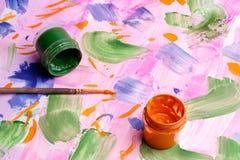 Zwei Dosen der Farbengouache auf dem gemalten Papier, der Bürste für das Zeichnen und des umgeworfenen Behälters mit Farbe für da Stockbild