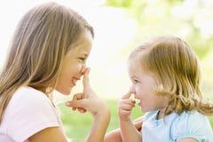Zwei draußen spielende und lächelnde Schwestern Lizenzfreies Stockbild