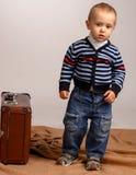 Zwei, drei Jahre alte Baby tragen den großen Koffer, der auf einem w lokalisiert wird Lizenzfreie Stockbilder
