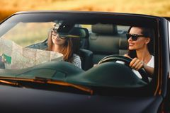Zwei dunkelhaarige junge Frauen sitzen einen schwarzen Cabriolet an einem sonnigen Tag Eins von ihnen hält Karte in ihren Händen lizenzfreie stockbilder