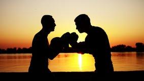 Zwei dunkle Männerfiguren, bei Sonnenaufgang, gegen das Licht, Verpacken, Fighting im Sparring, Training in einem Paar Techniken  stock video