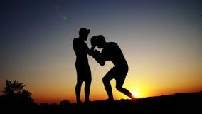 Zwei dunkle Männerfiguren, bei Sonnenaufgang, gegen das Licht, Verpacken, Fighting im Sparring, Training in einem Paar Techniken  stock video footage