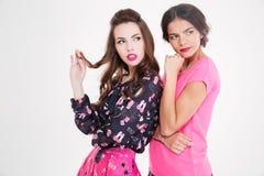 Zwei durchdachte attraktive junge Frauen, die zusammen stehen und weg schauen Lizenzfreies Stockfoto
