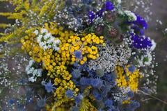 Zwei Eheringe auf einem Blumenstrauß von hellen blauen und gelben Blumen, Hochzeit, Antrag, Lebensstilkonzept Stockbilder