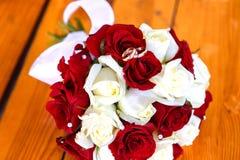 Zwei Eheringe an einem Blumenstrauß von roten und weißen Rosen Stockbild