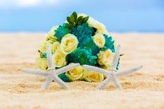 Zwei Eheringe mit zwei Starfish- und Hochzeitsblumenstrauß auf einem sandigen tropischen Strand Hochzeit und Flitterwochen in den Stockfotografie
