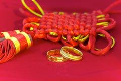 Zwei Eheringe und chinesischer Knoten Stockfotos