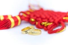 Zwei Eheringe und chinesischer Knoten Stockbilder