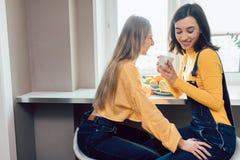Zwei ehrfürchtige klatschende Mädchen beim Trinken des Kaffees stockbild