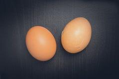 Zwei Eier auf schwarzem Hintergrund Eins ist gebrochen Lizenzfreie Stockfotos