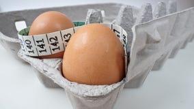 Zwei Eier im Karton mit messendem Band 2 Stockbild