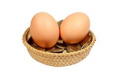 Zwei Eier mit Münzen in einem Korb Stockbilder