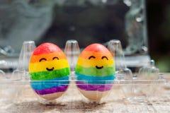 Zwei Eier werden in den Farben des Regenbogens als Flagge von Homosexuellen und von Lesben sowie von Ostereiern gefärbt Homosexue stockfotos