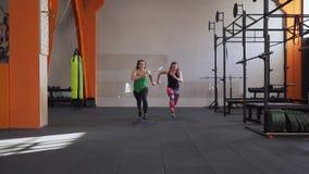 Zwei Eignungsfrauen konkurrieren beim Laufen in Turnhalle stock video