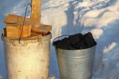 Zwei Eimer, die mit Kohle und Holz gefüllt werden, stehen auf dem Schnee lizenzfreie stockbilder
