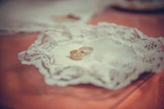 Zwei einfache goldene Eheringe auf kupfernem Präsentierteller Stockfotografie