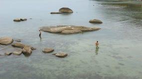 Zwei einsame Männer am steinigen Strand von KOH Samui Lizenzfreies Stockbild