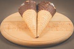 Zwei Eiscreme mit Kegel in der Schokolade auf einer runden Eiscreme Holzbock/zwei mit Kegel in der Schokolade auf einem runden Ho lizenzfreie stockbilder