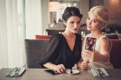 Zwei elegante Damen, die selfie im Restaurant nehmen Lizenzfreie Stockfotografie