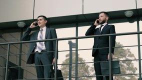 Zwei elegante Geschäftsmänner, die Geschäft an den Handys stehen nahe dem Bürogebäude tätigen stock video