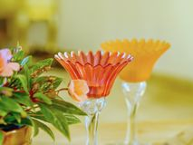 Zwei empfindliche Glaskerzenständer in den empfindlichen Farben mit Blumen zur Seite, ein Stillleben stockbilder