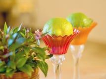 Zwei empfindliche Glasschiffe in den empfindlichen Farben mit Blumen zur Seite und innerhalb einer frischen Zitrusfrucht stockfotografie