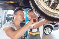 Zwei engagierte Automechaniker, die ein Auto abstimmen Stockfoto