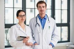 Zwei engagierte Doktoren, die an der Kamera lächeln Stockfoto