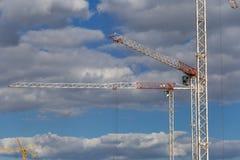 Zwei enorme Baukräne auf einer Baustelle stockbilder