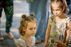 Zwei entzückend wenige Mädchen auf dem Spielplatz, der mit nachdenklichen Gesichtern steht stockbilder