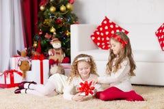 Zwei entzückende gelockte Mädchen, die mit Geschenkbox spielen Stockfotos
