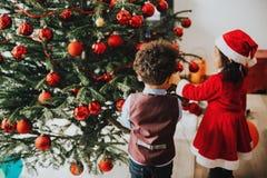 Zwei entzückende 3-Jährige Kinder, die durch den Weihnachtsbaum spielen stockfoto