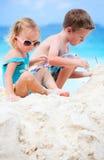 Zwei entzückende Kinder, die zusammen am Strand spielen Stockfotografie