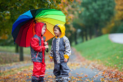 Zwei entzückende Kinder, Jungenbrüder, spielend im Park mit umbrel lizenzfreie stockfotografie