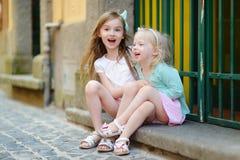 Zwei entzückende kleine lachende und umarmende Schwestern Stockfoto