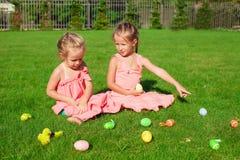 Zwei entzückende kleine Mädchen, die mit Ostereiern spielen Stockfotos