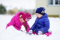 Zwei entzückende kleine Mädchen, die Spaß zusammen im schönen Winterpark haben Schöne Schwestern, die in einem Schnee spielen Stockfotografie